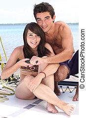 Closeup of a young couple sailing a catamaran