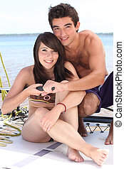 Closeup of a young couple sailing a catamaran