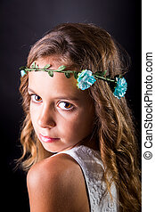 Closeup of a young girl with flower tiara and sober look