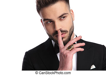 man in tuxedo with finger over his mouth is thinking