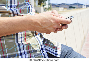 young man using a smartphone outdoors