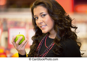 Closeup of a young woman holding apple