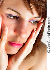 Closeup of a young woman holding her face with hands