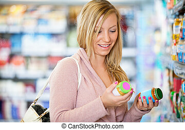 Closeup of a young woman smiling while holding jar in the...