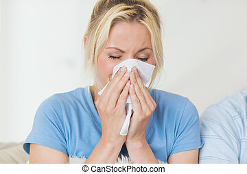 Closeup of a young woman suffering from cold with eyes...