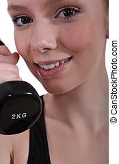 Closeup of a young woman with a dumbbell