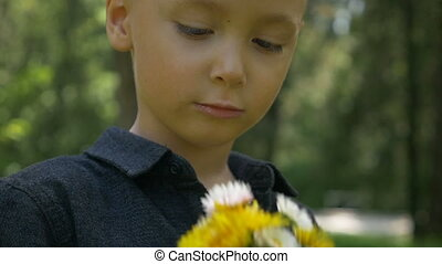 Closeup of adorable kid smelling spring flowers and feeling...