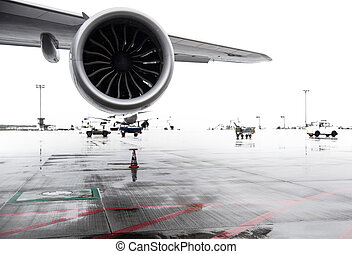 airliner jet wing and engine on airport apron on rainy day