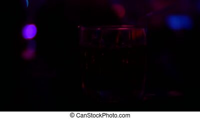 Closeup of alcohol cocktail in glass on bar counter, in nightclub. background blur,