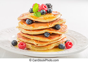 Closeup of american pancakes with berries on white background