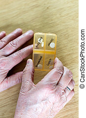 Closeup of an elderly senior woman's hands taking her medication for the week in a pill box on wooden table, business,health concept