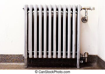 Closeup of an old radiator with a new thermostat - close up...