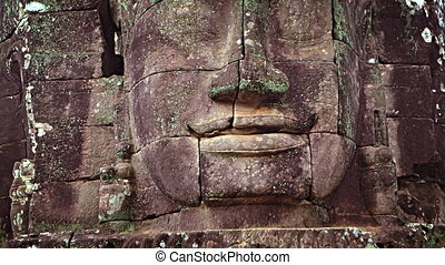 Closeup of Ancient Stone Face at Bayon Temple in Cambodia -...