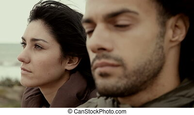 Man and woman angry at each other talking in front of the ocean film look closeup