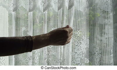 Closeup of Anonymous Woman Admiring Lace Window Curtains -...