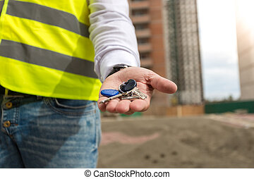 Closeup of architect on building site holding keys from new home