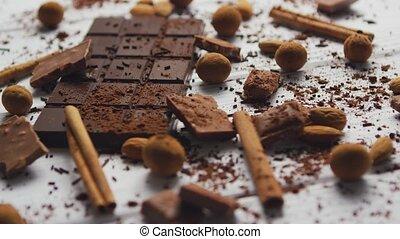 Closeup of arranged mess of black chocolate bar with milk ...