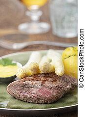 closeup of asparagus on a steak