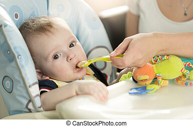 Closeup of baby boy eating puree from spoon - Closeup ...