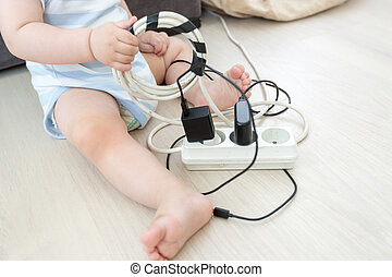 Closeup of baby boy pulling out cables from electrical extension