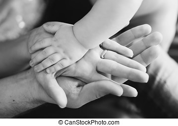Closeup of baby's and parent's hands. black and white...
