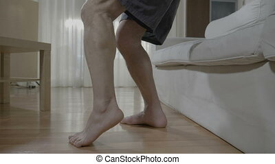 Closeup of barefoot senior man having muscle discomfort on leg while he standing up from couch