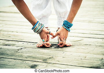 closeup of barefoot woman feet and hands practice yoga...