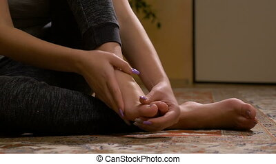 Closeup of barefoot young woman massaging her sprained foot having painful symptoms