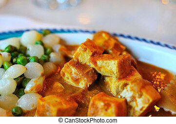Closeup of Oriental style bean curd topped with spicy sauce.