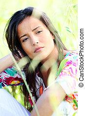 Closeup of beautiful brunette girl sitting in meadow