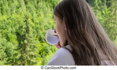 Closeup of beautiful brunette woman drinking coffe in morning and looking on pine forest. Concept of people traveling, tourism and vacation in mountains at summer.