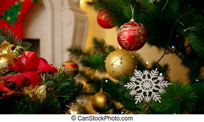 Closeup of beautiful Christmas tree decorated with colorful baubles and snowflakes