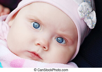 Closeup of beautiful cute little girl is in carriage