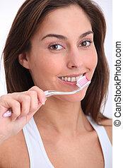 Closeup of beautiful woman brushing her teeth