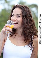 Closeup of beautiful woman drinking orange juice