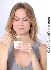 Closeup of beautiful woman eating yogurt