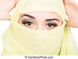 Closeup of beautiful young arabian woman in yellow hijab. Charm and beauty of the East.