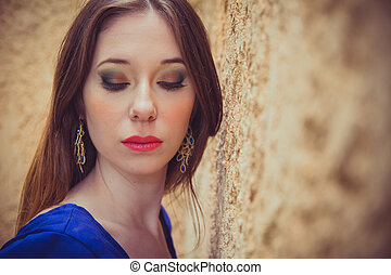 Closeup of beautiful young brunette woman posing outdoor standing next to a wall