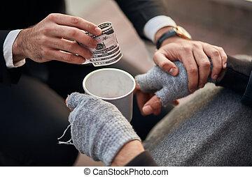 Closeup of beggar man's hands sit on walking street and need help