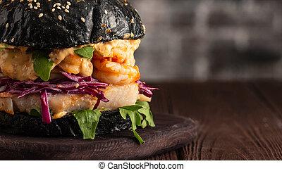 Closeup of Black burger with fish and shrimps. Fishburger with prawns
