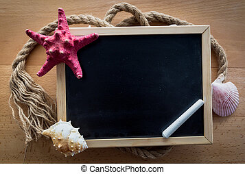 Closeup of blackboard decorated with seashells and red starfish