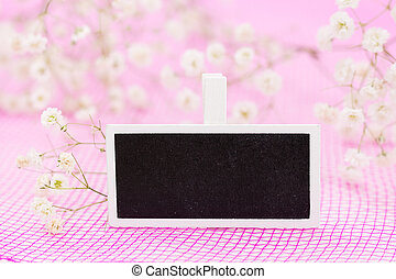 Closeup of blank blackboard sign with white flowers, on pink background and copy-space.