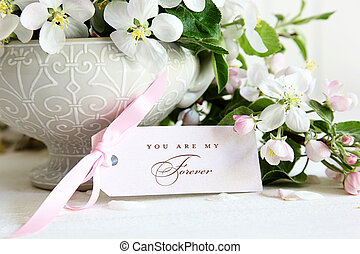 Closeup of blossom flowers in vase with gift card