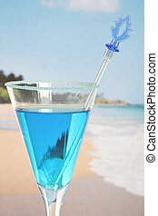 Closeup of blue cocktail with tropical beach background