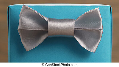 Closeup of blue paper gift box with silver ribbon bow on oak table