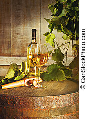 Closeup of bottle of white wine with glass on barrel