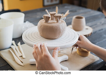 Closeup of bottom of mug, which is being decorated in ceramic studio. Female professional hands making clay dots or drops on the surface of vase by special squeezing tool.