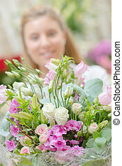 Closeup of bouquet of flowers, woman in background