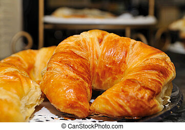 closeup of breakfast croissants with other pasteries in the background