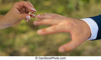 closeup of bride and groom exchanging wedding rings over green nature background